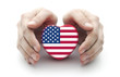 Hands covering U.S. heart on white background