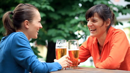 Two female friends talking and drinking beer, slow motion