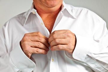 man closing his shirt