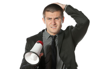 Portrait of angry young business man holding megaphone.