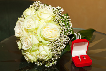 bridal bouquet and a box with the rings on a glass table