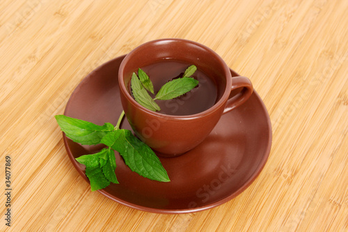 Cup of green tea on the saucer with mint on wooden surface