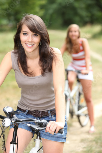 Two girls riding bikes through the forest