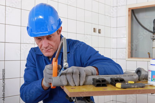 Builder sawing a tube