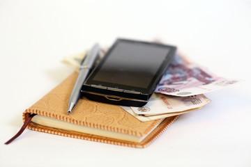 Блокнот, деньги, телефон и ручка