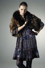 High fashion model in winter fur coat clothes posing