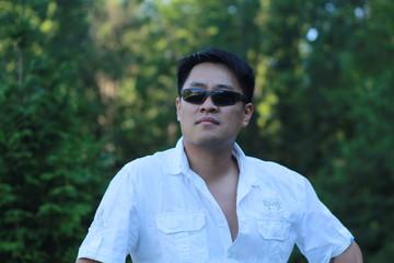 Asian man wearing sunglasses looking forward