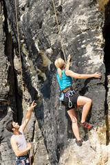 Rock climbing male instructor blond woman sunny