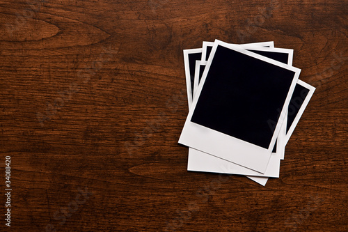 Empty instant photos on wooden table background