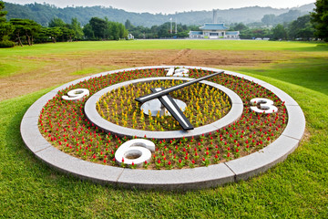 Round flower clock on lawn background