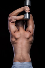 Male back doing fit exersices with dumbbell