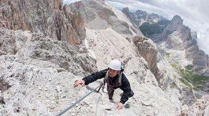 Rock climber with helmet. Dolomites, Italy
