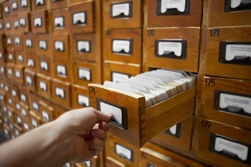 database concept. vintage cabinet. human hand opens library card