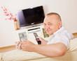 Smiling aged man watching TV