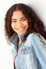 Portrait of smiling teenager leaning on wall