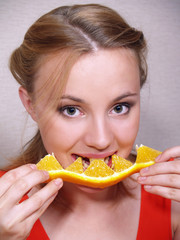 beautiful girl eats an orange segment