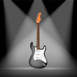 black electric guitars on spotlight background