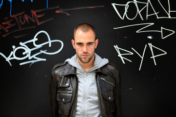 Portrait of bad boy standing on tagged wall