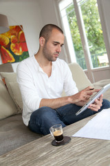 Man working at home with electronic tablet