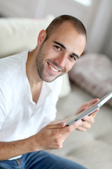 Closeup of handsome man websurfing on touchpad