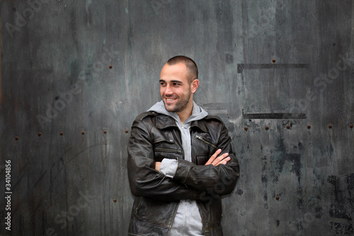 Man with leather jacket standing on metal door