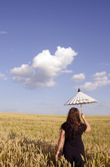 Young woman walking in the field of wheat.