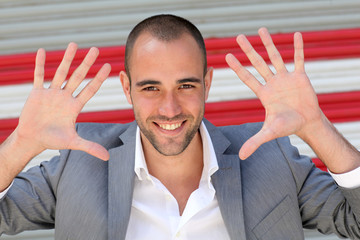 Attractive man showing hand palms to camera