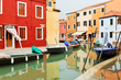 Houses and boats reflected in the water in Venice, Italy