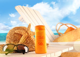 Sunblock lotion and beach items on table poster