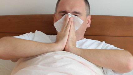 Ill man with a flu coughing ang using hand tissue