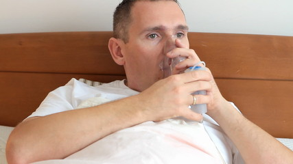 Sick man using inhaler also called nebulizer