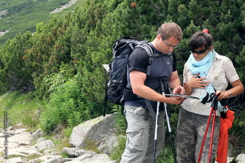 Young couple of hikers with compass and map in the mountains