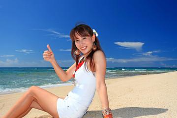 真っ白い砂浜に座りガッツポーズをしている笑顔の女性