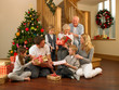 Family exchanging gifts in front of Christmas tree