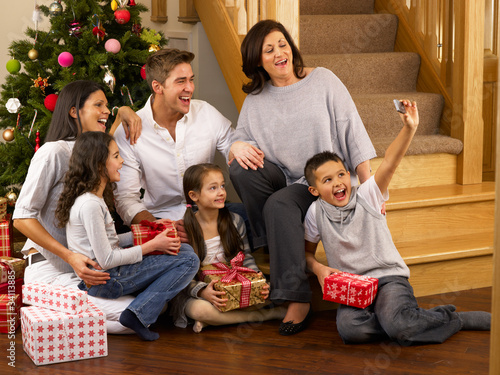 Hispanic family taking photos at Christmas
