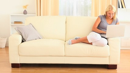 Blonde woman relaxing on the sofa with a notebook