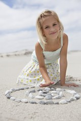 Portrait of a girl playing with pebbles on beach