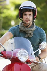 Portrait of a young man sitting on a motor scooter