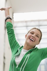 Excited woman looking away with arms raised