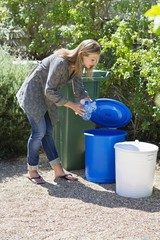 Woman throwing water bottles in garbage bin