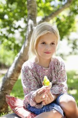 Cute little girl holding a toy outdoors