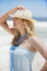 Mid adult woman wearing sunhat on the beach