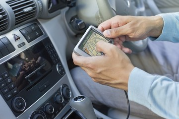 Close-up of human hand using GPS navigation system in car