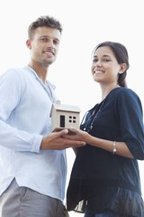 Portrait of a young couple holding small model house