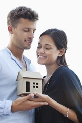 Cute young couple holding small model house