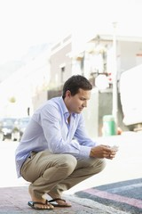 Man crouching and text messaging on a mobile phone