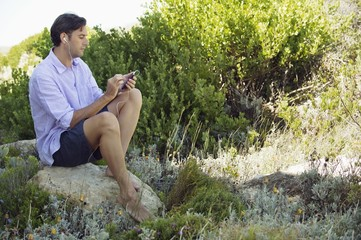 Mid adult man sitting on a rock and listening to music with an MP3 player