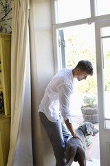 Side profile of a man standing at door with dog