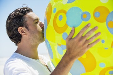 Side profile of a man blowing beach ball