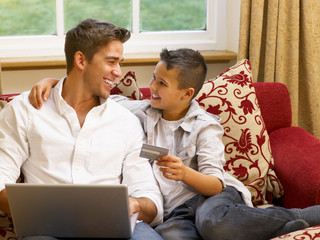 Hispanic father and son shopping online